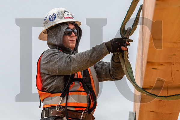 Timberland Inc. carpenter Jesus Antonio removes rigging from a glulam beam. (Josh Kulla/DJC)