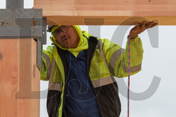 Marcos Rosas secures a glulam beam inside a steel bracket. (Josh Kulla/DJC) (Josh Kulla/DJC)