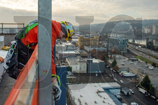 Kali Kalugin, an apprentice carpenter with Local 146 and employee of Performance Contracting Inc., caulks facade on the 5 MLK mixed-use building in Southeast Portland. (Josh Kulla/DJC)