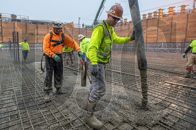 Ian Malsbury, foreground, and Rogelio Estrada, both journeyman cement masons with Local 555 and LaRusso Concrete employees, pour concrete at the Saltwood North mixed-use project in Northwest Portland. (Josh Kulla/DJC)