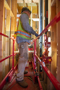 Rod Main, a journeyman sprinkler fitter with Local 669 and an employee of Centurion Fire Protection, inspects a fire protection line in a crawl space. (Josh Kulla/DJC)