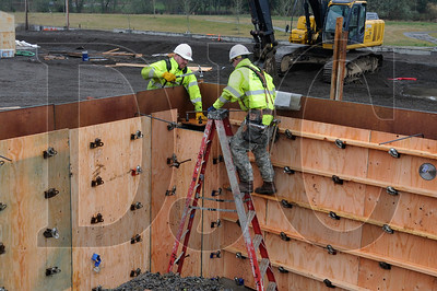 Mac Riskey, left, and Brian Tatro, both carpenters with Todd Construction, set bolts on a foundation wall at the site of the Stafford Hills club in Tualatin Wednesday.