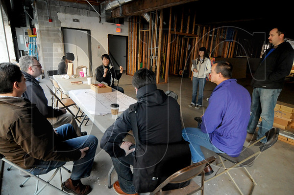 Victoria Frey, fourth from left, executive director of the Portland Institute for Contemporary Art, speaks during a project meeting at the group's future West End headquarters Monday. Multiple general contractors and subcontractors that are usually competitors are working side-by-side on a pro bono basis to complete the renovation.