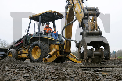 Jason Glenn, a foreman for underground utilities with Northwest Earth Movers, uses a hoe pack to compact dirt over a stormwater pipe at the site of the Stafford Hills club in Tualatin Wednesday. The $18.5 million athletic club is being built by Todd Construction, and is slated for completion by late November.