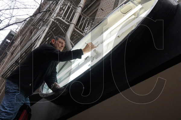 Rick Lent, a sign technician with Security Signs, marks the date on a fluorescent bulb while installing a sign for a new Under U 4 Men location in downtown Portland Friday. The boutique men's underwear retailer is opening a new 5,000-square-foot store at the corner of Southwest Washington Street and Park Avenue.