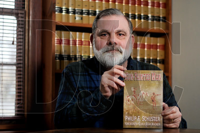 """Attorney Phil Schuster holds a copy of his book, """"Sun-Painted Man,"""" at his Northeast Portland practice Tuesday."""