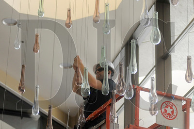 Miriel Aguirre, a journeyman electrician with O'Neill Electric and a member of IBEW Local 48, installs a chandelier designed to resemble raindrops at the Marriott Downtown Waterfront Tuesday in Southwest Portland. Abbott Construction is performing an extensive remodel on the hotel's lobby, restaurants, and conference rooms.