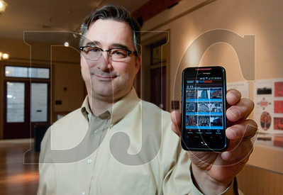 Val Ballestrem, education manager for the Bosco-Milligan Foundation, holds a smartphone displaying an application which