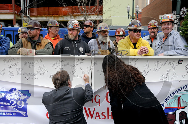 Ironworkers congregate around the beam as ceremony attendees add their signatures.
