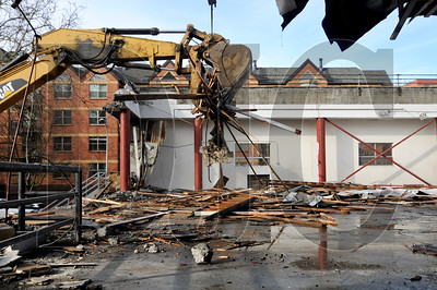 Crews with Konell Construction & Demolition Corp. demolish the former University Station post office building in downtown Portland.