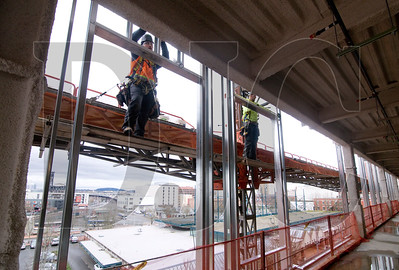 Western Partitions employees Daniel Tracy, let, a journeyman carpenter with Local 146, and Tyler Kehoe, a sixth-term apprentice, install exterior framing on the building's fourth floor.