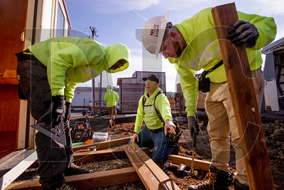 Torre Sathrum, center, a Northwest College of Construction instructor, guides POIC students Abdul Abdullahi, left, and Austin Smith in building a landing outside the entry to a pod at Kenton Women's Village. (Sam Tenney/DJC)