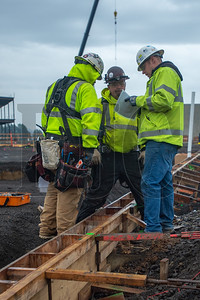 Carpenters discuss site plans at the Sherwood High School job site. (Josh Kulla/DJC)