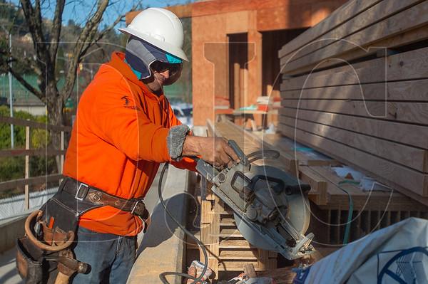 Journeyman carpenter Johnny Hongun, an employee of Advanced Pro Builders, cuts a floor joist. (Josh Kulla/DJC)