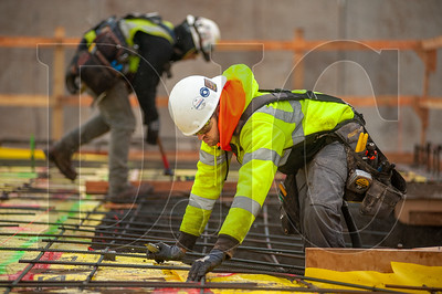 Jeff Nevin, an apprentice carpenter with Local 1503 and an employee of Skanska USA Builders, installs vapor barrier at the Sherwood High School job site. (Josh Kulla/DJC)