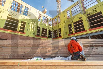 Journeyman carpenter Johnny Hongun, an employee of Advanced Pro Builders, unwraps a stack of floor joists. (Josh Kulla/DJC)