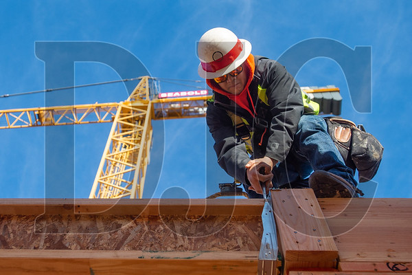 "Journeyman carpenter Carlos ""Charlie"" Ramirez, an employee of Advanced Pro Builders, secures a floor joist while framing the Koz on SW Fourth Avenue building. (Josh Kulla/DJC)"
