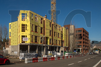 The Koz on SW Fourth Avenue mixed-use building is begin erected on the site of a former surface parking lot at the south end of downtown Portland. (Josh Kulla/DJC)