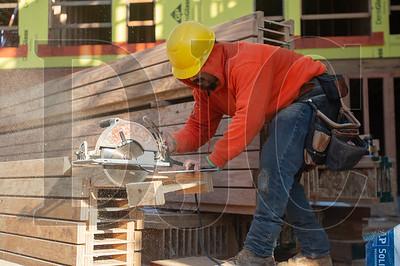 Jose Lopez, a carpenter with Advanced Pro Builders, cuts a floor joist.