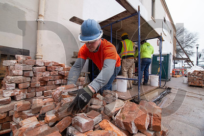 Seth Callaway, a journeyman pointer/cleaner/caulker with BAC Local 1 and a foreman with Pioneer Waterproofing, stacks bricks removed from the Hallock-McMillan Building. (Sam Tenney/DJC)