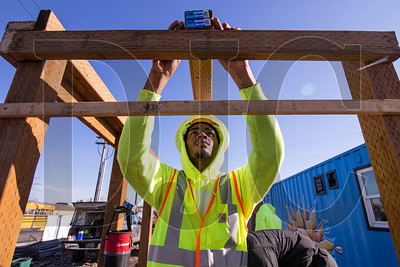 Trevon Moore, a pre-apprenticeship student with the Portland Opportunities Industrialization Center, aligns material while building a trash enclosure at the Kenton Women's Village in North Portland. (Sam Tenney/DJC)