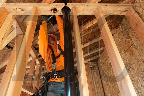 Greg Hallstrom, a fourth-year apprentice plumber with Atlas Plumbing, installs piping to serve a toilet, sink and shower on the floor above. (Josh Kulla/DJC)