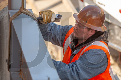 Kenny Basler, a journeyman ironworker with Madlyn Metal Fab, secures a steel beam in place at the Koz on SW Fourth Avenue mixed-use project. (Josh Kulla/DJC)