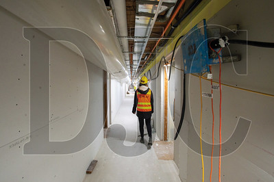 Laura Waddick, a project engineer with Walsh Construction Co. inspects the fourth floor corridor at the Rennaissance affordable housing project. (Josh Kulla/DJC)