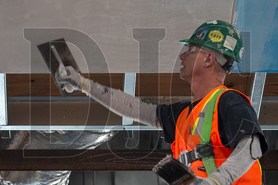Bert Carter, a journeyman plasterer with Local 82 and an employee of Performance Contracting Inc., applies a coat of veneer plastic to a soffit. (Josh Kulla/DJC)