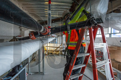 David Beseau, a journeyman plasterer with Local 82 and an employee of Performance Contracting Inc., covers pipes with plastic sheeting as he installs fireproofing on a mezzanine level. (Josh Kulla/DJC)