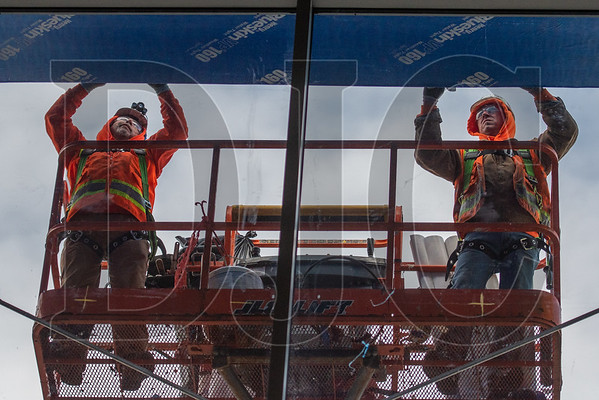Union carpenters with Performance Contracting Inc. apply weather barrier to an exterior soffit. (Josh Kulla/DJC)