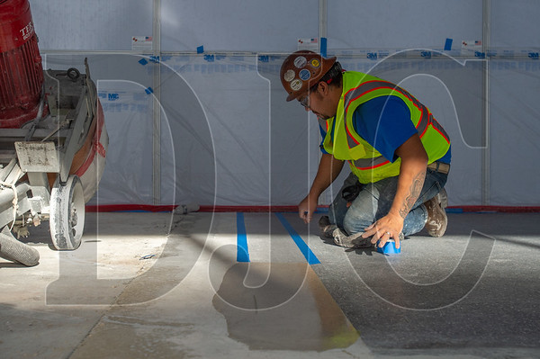 Jorge Torres, a journeyman tile layer with BAC Local 4 and an employee of Top End Terrazo of Los Angeles, installs terrazo flooring in the middle of the concourse. (Josh Kulla/DJC)