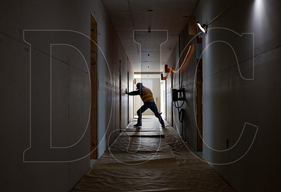 Darren Anstine, a journeyman laborer with RDF Builders and a member of Local 737, rolls out protective covering on a fifth-floor hallway.
