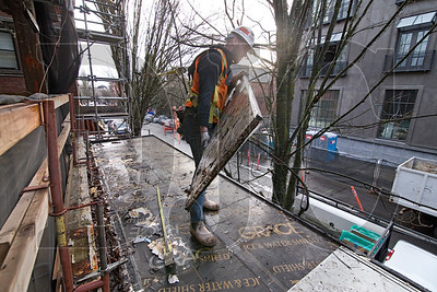 Kenneth Fuller, an employee of  Tradesmen International, performs demolition work on a canopy at 2281 Glisan.