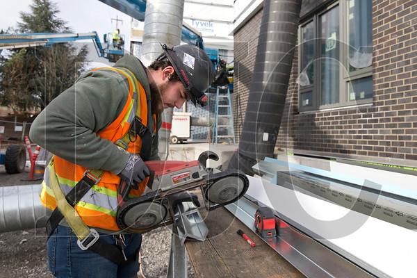 Pioneer Sheet Metal employee Josh Castillo cuts furring channel.