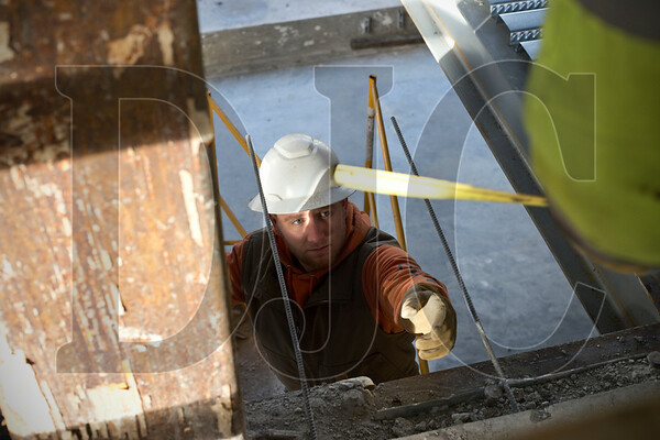 Rob Kalleck reaches for a tape measure to take measurements for a notch to be cut in pan decking.