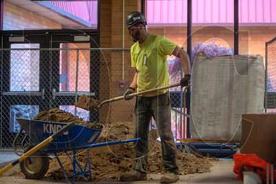 Earl Crawford, an apprentice plumber with Caliber Plumbing, removes dirt from a trench being excavated for drainage lines at Five Oaks Middle School. (Josh Kulla/DJC)