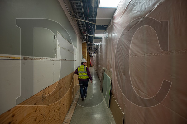 Beaverton School District Project Manager Jessica Pavelka walks through a section of Five Oaks Middle School that has been partitioned off to allow construction activity while school is in session. (Josh Kulla/DJC)