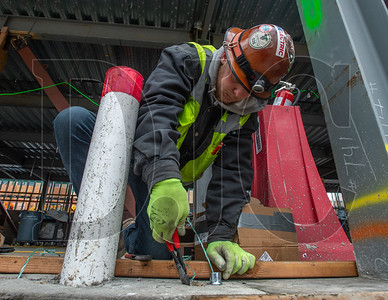 Tyler Klement, an apprentice electrician with Prairie Electric, runs wire through conduit in the new auxiliary gym at Tigard High School. The campus is undergoing a two-phase, $66 million renovation and expansion project. (Josh Kulla/DJC)