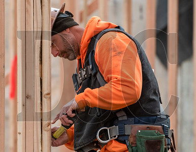 Journeyman carpenter Jeremy Laperl,, an employee of DSL Builders, takes a measurement while framing interior walls at Tigard High School. (Josh Kulla/DJC)