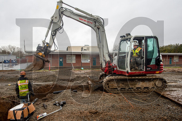 Kyle Ek, right, a journeyman plumber and crew foreman with Piper Mechanical, backfills a wastewater line trench. (Josh Kulla/DJC)
