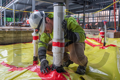 Apprentice carpenter John Holley, a member of Local 1503 and an employee of Pence Kelly Construction, caulks a seam in the weather barrier around a water line. (Josh Kulla/DJC)