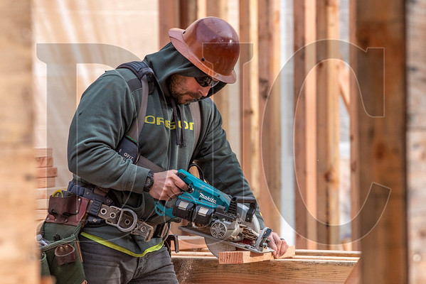Journeyman carpenter Judah Webb, an employee of DSL Builders, cuts lumber while framing interior walls at Tigard High School. (Josh Kulla/DJC)