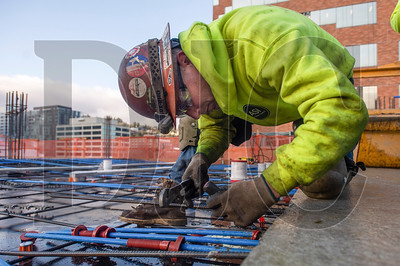 Bobby Palmersheim, a journeyman ironworker with Local 29 and an employee of R2M2 Rebar and Stressing, prepares post-tension cables for a slab pour at the 140 Columbia mixed-use project. (Josh Kulla/DJC)