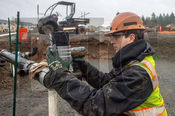 Apprentice plumber Jed Redinger of Piper Mechanical assembles a wastewater branch line. (Josh Kulla/DJC)