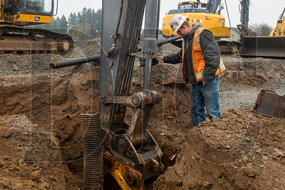 Mike Coe, a crew foreman with Nutter Excavation, guides the excavation of a trench for underground utility piping. (Josh Kulla/DJC)