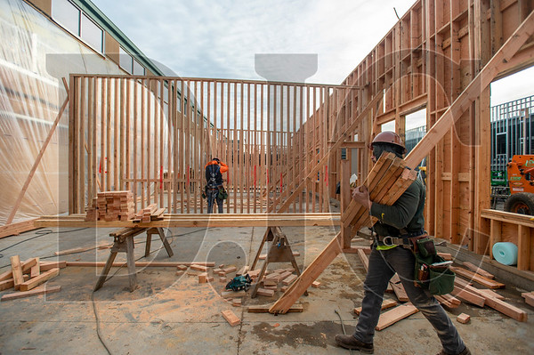 Journeyman carpenter Judah Webb, an employee of DSL Builders, carries lumber as his crew frames interior walls at Tigard High School. (Josh Kulla/DJC)