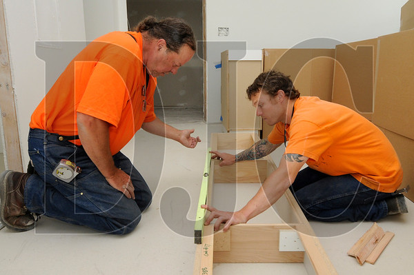 R&H Construction employees Mike Dedrickson, left, a journeyman carpenter, and Adam Travis, an apprentice carpenter, install cabinets in a residential unit at the Killingsworth Station development in North Portland on Wednesday.