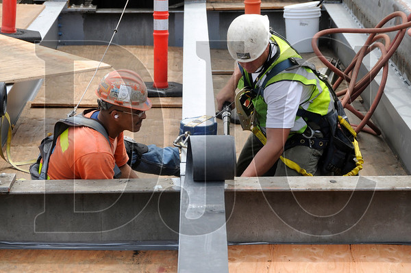 Conway Construction employees Chris Roebuck, left, a laborer and member of Laborers' Local 320, and ironworker Matt Briney, tighten I-beam bolts while working on the Morrison Bridge Rehabilitation project on Monday.
