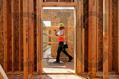 Wood Mechanix carpenter Alex Auilez carries a roof truss.